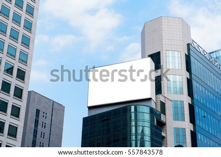 Blank advertising billboard on top of modern building in the city with blue sky background useful for products advertisement