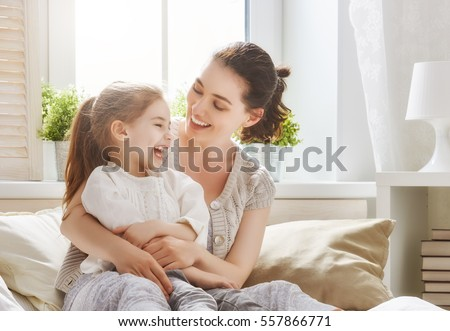 Happy loving family. Mother and her daughter child girl playing and hugging. Royalty-Free Stock Photo #557866771