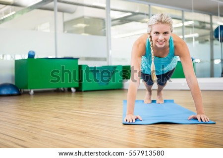 Fit blonde planking on mat in fitness studio #557913580