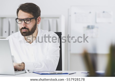 Close up of a bearded businessman wearing glasses and sitting at his laptop and typing. There is a whiteboard and a bookcase in the background. #557928178