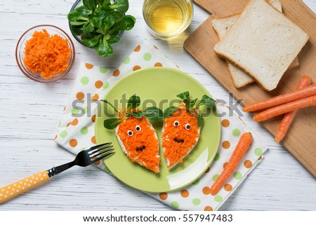 Funny toasts in a shape of carrots, food for kids Easter idea, top view #557947483