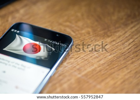 Smartphone on wooden background with 5G network sign 25 per cent charge and Japan flag on the screen. #557952847