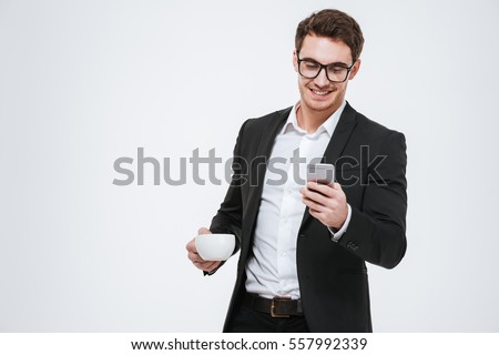 Portrait of a smiling young business man using smartphone and holding cup of coffee isolated on a white background