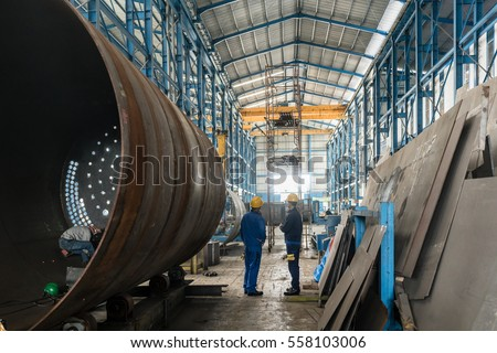 Two workers wearing yellow hard hat and blue uniform in the interior of an industrial hall #558103006