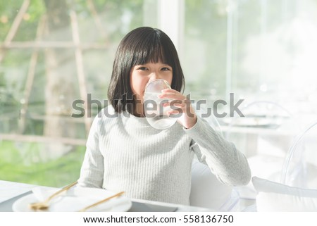 Beautiful Asian girl drinking  glass of water in a restaurant #558136750
