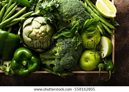 Variety of green vegetables and fruits in a crate on the table #558162805