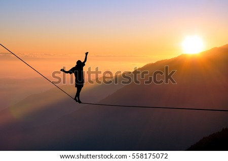 Silhouette of young man balancing on slackline high above clouds and mountains, sun, beautiful colorful sky and clouds behind. Slackliner balancing on tightrope between two rocks, highline silhouette. Royalty-Free Stock Photo #558175072