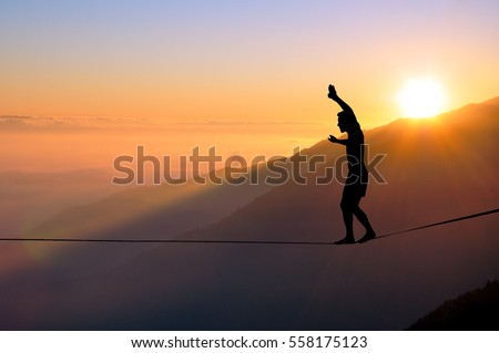 Silhouette of young man balancing on slackline high above clouds and mountains, sun, beautiful colorful sky and clouds behind. Slackliner balancing on tightrope between two rocks, highline silhouette.