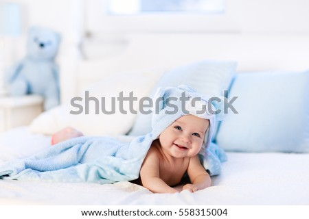 Baby boy wearing diaper and blue towel in white sunny bedroom. Newborn child relaxing in bed after bath or shower. Nursery for children. Textile and bedding for kids. New born kid with toy bear Royalty-Free Stock Photo #558315004