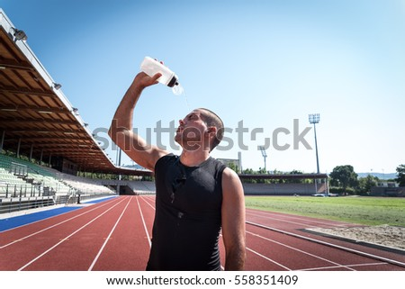 Runner pouring water on his face after the run #558351409