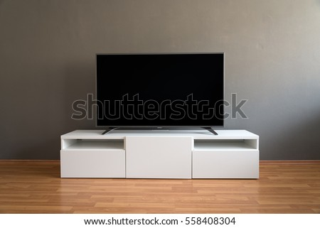 Flat LCD television on white cabinet in the living room with dark gray wall and parquet floor #558408304