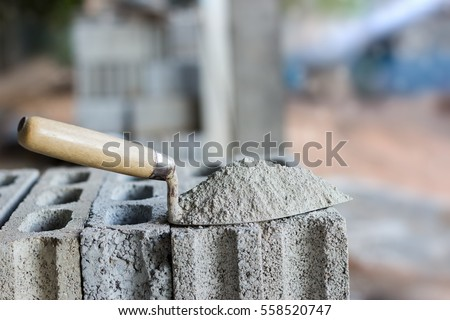 Cement or mortar, Cement powder with a trowel put on the brick for construction work. Royalty-Free Stock Photo #558520747