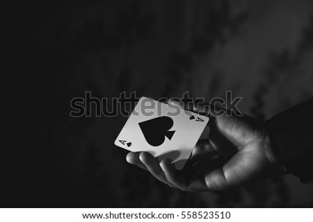 Ace Spade Card in Hand, Low-key lighting Royalty-Free Stock Photo #558523510