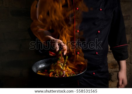 Professional chef and fire. Cooking vegetables and food over an open fire on a dark background. Hotel service photo background. Horizontal view.