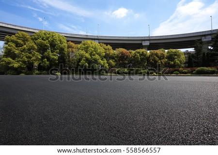 Empty road floor surface with city viaduct overpass bridge background #558566557