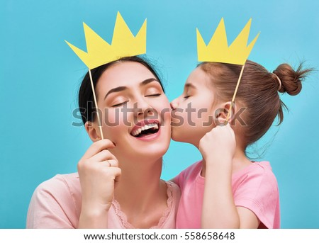Funny family on a background of bright blue wall. Mother and her daughter girl with a paper accessories. Mom and child are holding paper crown on stick. Royalty-Free Stock Photo #558658648