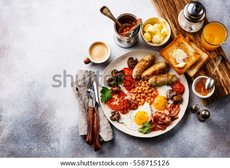Full English breakfast with fried eggs, sausages, bacon, beans, toasts and coffee on copy space background #558715126