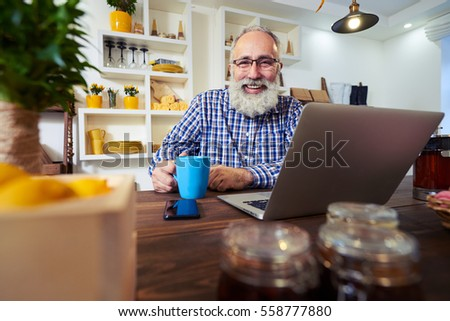 Side low angle of man looking at the camera. Wearing casual checked shirt and wearing glasses. Teapot, jars of jam and a box with lemons standing on the table  #558777880