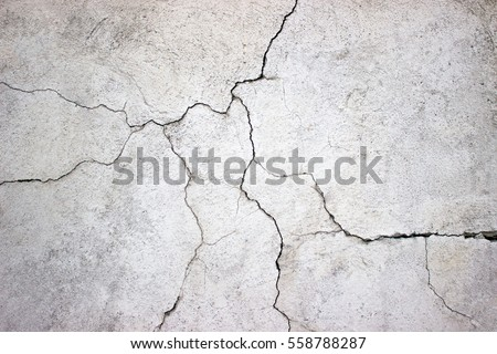cracked concrete wall covered with gray cement surface as background Royalty-Free Stock Photo #558788287