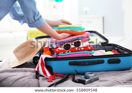 Female hands packing traveler case on bed, closeup Royalty-Free Stock Photo #558809548