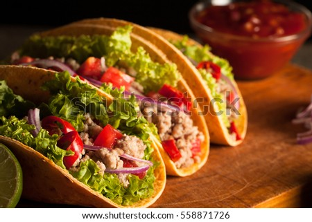 Photo of Mexican tacos with ground beef, onion, tomatoes, chili, red sauce, lettuce and lime on wooden background. Spicy and fast food concept. #558871726