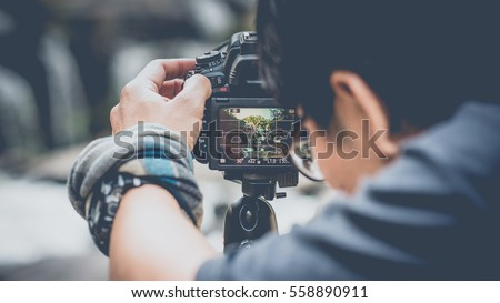 The photographer to pay close attention to take a photo. (vintage style)   Royalty-Free Stock Photo #558890911