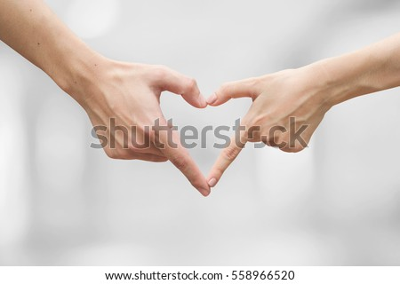close up man and woman hands making heart shape for married concept.