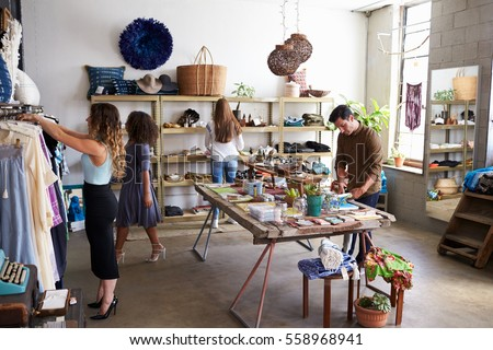 Customers and staff in a busy clothes shop Royalty-Free Stock Photo #558968941