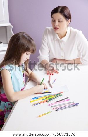 Happy beautiful mother teach her daughter to paint, painting and smiling and looking at camera. Studio shot. #558991576