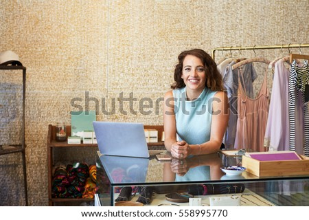 Young woman working in clothes shop leaning on counter Royalty-Free Stock Photo #558995770