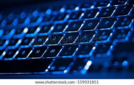 Closeup of laptop keyboard illumination, backlit keyboard Royalty-Free Stock Photo #559031851