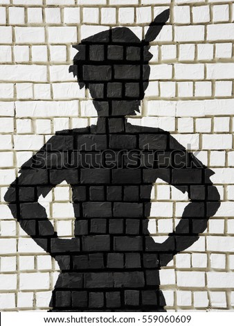 Painted silhouette black Peter Pan on white brick wall, Public decoration with free copy space for text or background usage.