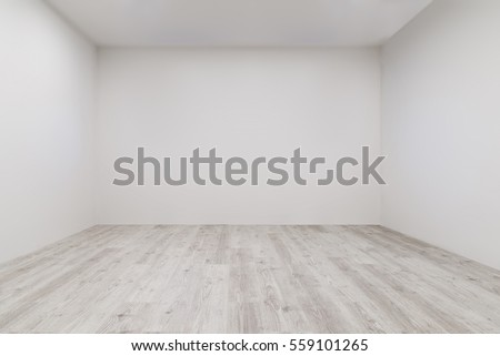 Empty room with whitewashed floating laminate flooring and newly painted white wall in background Royalty-Free Stock Photo #559101265