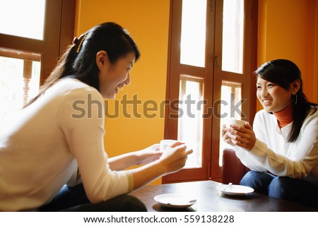 Two young women, holding cups of coffee, talking #559138228