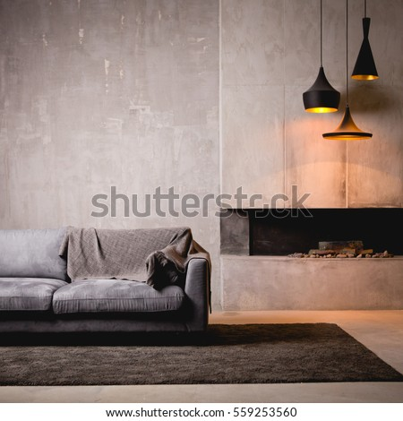 Gray velour sofa in a dark room the bright light from eternal light, and artificial fireplace. Interior loft with concrete walls #559253560