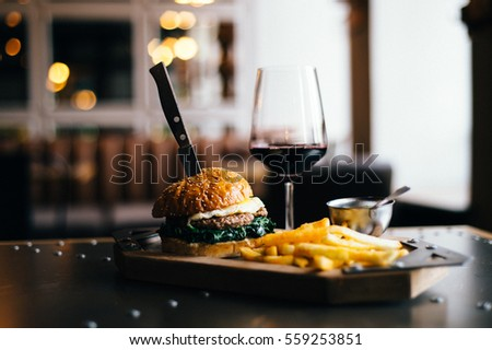 Prepare delicious fragrant golden sesame burger with fried egg spinach and meat cutlet placed on a table next to glass of red wine and fries golden potato with a knife stuck overall horizontal plan  #559253851