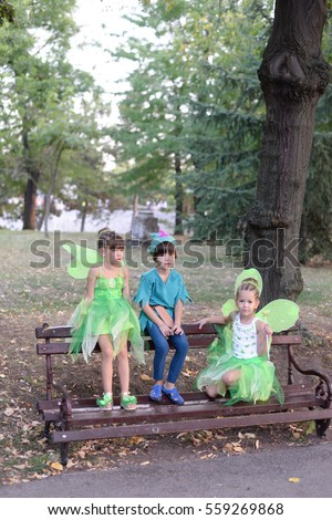 Boy and two girls in a green fairy costume with wings in the park. Kids in the park
