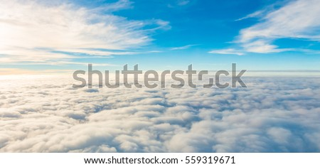 Sunrise above clouds from airplane window Royalty-Free Stock Photo #559319671