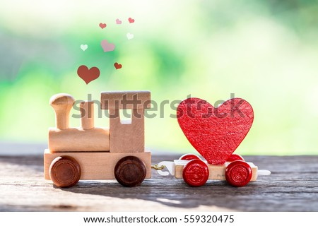 Red Heart Shape with Wooden Toy Train on wooden floor over blurred green garden  background,Image to Valentine Day concept.