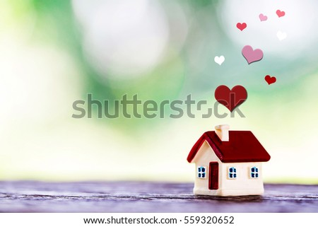 miniature house with red roof on wooden mock up over blurred green garden on day noon light.Image for property real estate investment concept.