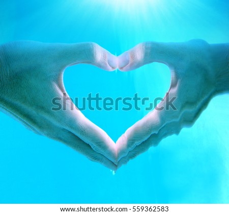 Hands of woman make heart shape sign underwater in swimming pool with clear blue water and sunrays on top,Happy valentines day concept and copy space. Note:Visible grain at 100%, best at smaller sizes #559362583