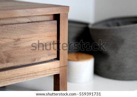 Timber bedside table with fabric storage tubs and marble storage box in a bedroom #559391731