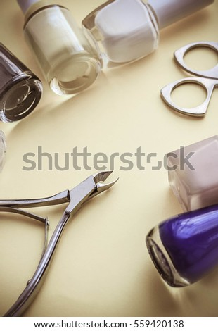 Manicure scissors and a nail on a yellow background #559420138