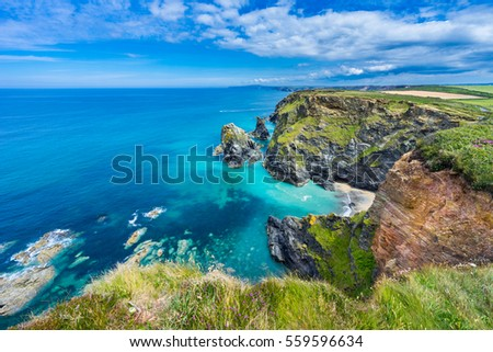 View of the South Devon coast, England, in the summer with clear waters, blue sky and grass. Royalty-Free Stock Photo #559596634