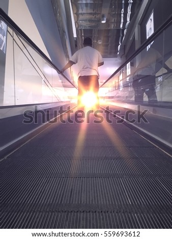 A man standing on escalator and holding the railing. Special tone and effect filters with rays of light and sun glare. #559693612