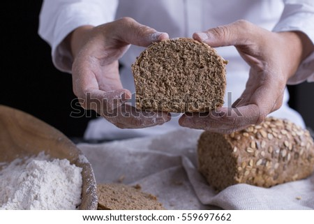 Whole grain bread put on kitchen napkin decorated with almond with a chef holding dough roller at the background. #559697662