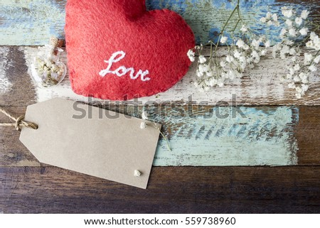 Love concept of blank brown paper tag with red heart and flowers on old wood for valentines day and wedding #559738960