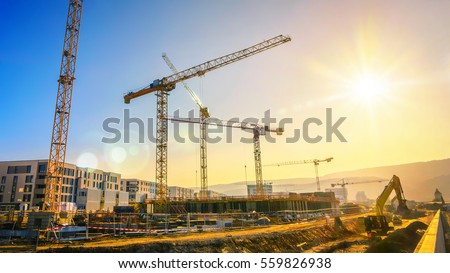 Large construction site including several cranes working on a building complex, with clear blue sky and the sun #559826938