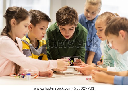 education, children, technology, science and people concept - group of happy kids building robots at robotics school lesson #559829731