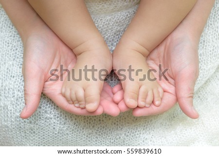 Mother holds baby's legs #559839610